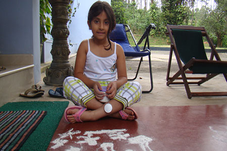 Image of a young guest trying out Rangoli Designs
