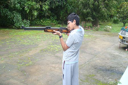 Image of a young boy firing an air rifle.