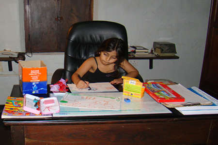 Image of a young girl absorbed in her painting